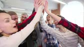 Cheerful team of people doing high five after playing table football