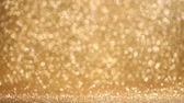 Shiny golden bokeh glitter lights abstract background, Christmas New Year party celebration concept Vídeos