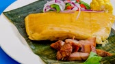 cubano : Tamal or tamales a traditional Latin American dish served with onions,pork and corn on the cob, all over a plantain leaf.