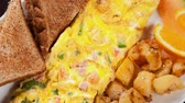 omelete : Delicious omelette with ham,peppers and cheese served with toasts and potatoes for a wonderful lunch snack