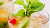 refrescante : Close up of a famous Cuban Mojito or also the Mint Julep, alcoholic refreshing drinks served with cold with ice and garnished with mint leaves,lime wedge and red cherry.
