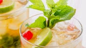 cubano : Close up of a famous Cuban Mojito or also the Mint Julep, alcoholic refreshing drinks served with cold with ice and garnished with mint leaves,lime wedge and red cherry.