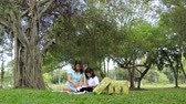 роман : Asian pregnant girl Is teaching a daughter to read books under a tree in a public park.