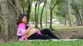 pat : Asian pregnant girl relax and sits under a tree in a pubic park. Stock Footage