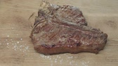 proteins : Seasoning is poured onto the finished juicy piece of steak. Fried meat on fire is on the board