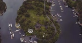 bird eye flight over island in fjord with yachts houses road