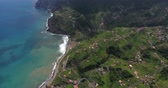 su damlası : Remote village with houses on the green hills by the sea, aerial view, Madeira, Portugal .
