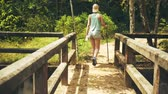 Girl is walking along an abandoned bridge in the jungle Стоковые видеозаписи
