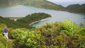 fű : tourist goes down a mountain path in dense vegetation with a beautiful view of the lake in the crater of a volcano