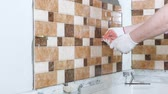 A worker is using plastic wedges to align the rows of ceramic tiles. Стоковые видеозаписи