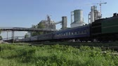 Passenger train is passing the cement plant.