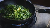 stirfry : woman is stirring vegetables in wok at kitchen Stock Footage