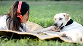 woman enjoys listening to music by headphone outdoor playing with friendly dog at sunset