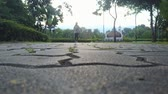 blurry view of woman jogging on street at public park, bottom view