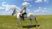 Young female sitting on the white horse outdoor under sky with clouds