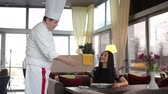 Chef serving delicious dish to female customer