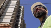 contramestre : Construction foreman in a helmet near the construction site. 4k video