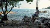 solitario : Man Sitting on Tree Swing At Beach By Tropical Ocean Archivo de Video