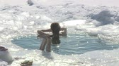 A girl bathes in an ice-hole