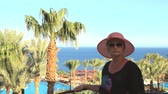 hoteleria : during a vacation on vacation, a young beautiful woman in a sun hat sits on the edge of the pool on a sunny summer day Archivo de Video