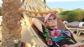 odpoczynek : on a sunny summer day, a beautiful young woman in a hat and black glasses from the sun is resting in a hammock on the sea in the shade of palm trees