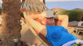 hamak : A young man in a cap from the sun is resting in a hammock on the seashore on a sunny summer day in the shade of palm trees Stok Video