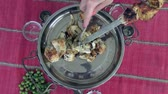 pinchos de carne : Ready skewers of various types of meat cooked on charcoal are removed from a skewer in a beautiful metal dish Archivo de Video