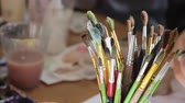 tela : different sized brushes for painting with oil paints stand in a glass on the table against the background of the artists hands painting, close-up