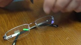 giymek : male hands take out glasses from a black case and wipe a glass lens with a rag from dust and dirt, close-up Stok Video