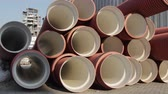 piping : Warehouse of finished plastic pipes industrial outdoors storage site. Manufacture of plastic water pipes factory. Process of making plastic tubes on the machine tool with the use of water and air Stock Footage