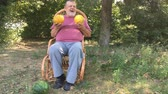 kavun : Ukrainian senior farmer shows two melons while sitting in a wicker chair outdoor