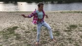 plezier : girl dancing on empty sand beach close to the river Stockvideo