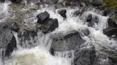 flowing water : water cascades on black stones at Urubamba river in Peru after heavy tropical rains, steady footage with original sound