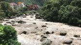 река : wild Urubamba River in Peru with Aguas Calientes town on backward, panoramic footage with natural sound