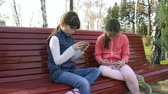 наркомания : digital device addiction. mobile phone apps. modern gadgets. young girls playing and browsing on smartphone park