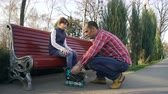 ojciec : father helping daughter dresses roller skates on bench in park. leisure time. parental care. family relations and support