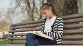 lavice : park leisure time. Young cute teen sitting bench reading book writing notebook. outdoor education.
