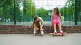 rolos : two girls active passtime in park. young teen dresses roller skates, sisters preparing skating. fun and joy leisure time.