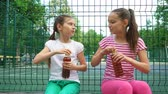сказать : Two caucasian children telling secrets, laughing and drinking in park, outdoors. leisure time park. Health, wellness, food concept