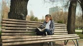 bank : park leisure time. Young cute tired teen lying and relax on bench with book. outdoor education.