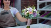 florystyka : professional florist presenting wedding bouquet in floral design studio. Caucasian female master in apron creating flower bunch composition. Floristry, handmade and small business concept