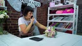 продавщица : Female florist talking on phone discussing cost of bouquet with customer in a flower shop. Ribbons, flowers, calculator on working table. shopping, sale, floristry and consumerism concept Стоковые видеозаписи