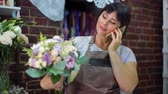 vendedora : Female florist talking on phone discussing cost of bouquet with customer in a flower shop. Ribbons, flowers, calculator on working table. shopping, sale, floristry and consumerism concept Vídeos
