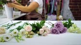 продавщица : Defocused female florist putting flowers on working table preparing to floral composition arrangement. shopping, sale, floristry, small business and consumerism concept