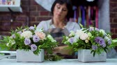 florystyka : professional florist arranging beatiful flower composition in wooden box in floral design studio. Caucasian female master in apron creating floral design. Floristry, handmade, small business concept