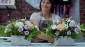florystyka : professional florist arranging beatiful flower composition in wooden box in floral design studio. Caucasian female master in apron showing floral design. Floristry, handmade, small business concept