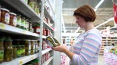 marináda : Caucasian woman near shop shelves and choosing marinade pickles jar in grocery market. female customer checking product ingredients. supermarket, sale, shopping, assortment, consumerism concept