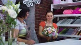 arranjando : professional florists arranging wedding bouquet in floral design studio. Caucasian women in aprons creating flower bunch composition. Floristry, handmade and small business concept