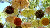 napernyő : lot of brightly orange and yellow umbrellas and balls hanging and moving in the wind in autumn in park. Street decoration, contemporary art, handmade concept Stock mozgókép