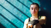 trener : Closeup portrait fit white female boxer sitting on floor near wall resting after training at gym free space, copyspace. Young brunette girl takes breake. Wellness, motivation concept Wideo